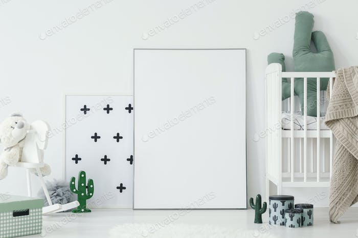 Cactus pillow in white cradle next to empty poster with mockup i