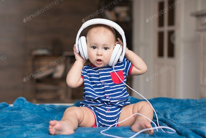Funny baby boy wearing white headphones