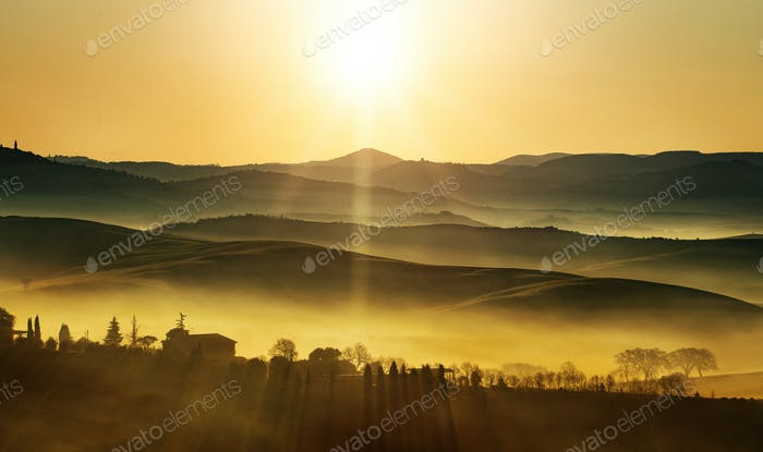 goldener Sonnenaufgang auf den nebligen Hügeln der Landschaft