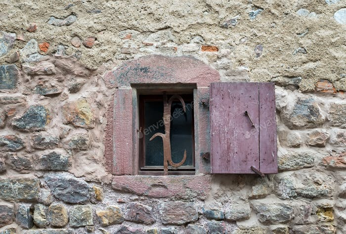 French window with closed old medieval wooden shutters in the village of Eguisheim, Alsace, France.
