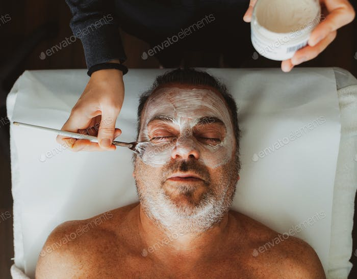 Middle-aged man in a spa with a facial mask.