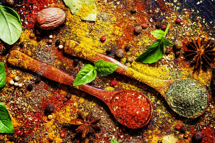 Food background, spices, dried herbs, anise, nutmeg and fresh green basil, top vie