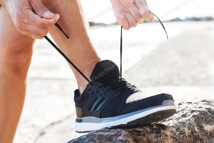 Close up of a man tying tying shoelace