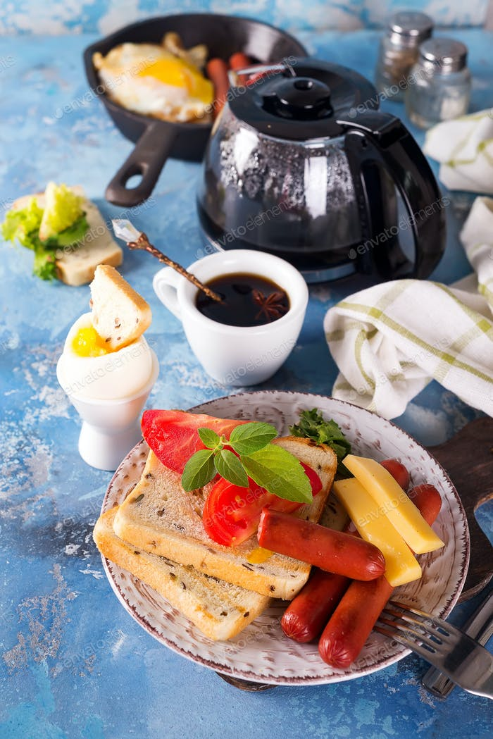 English breakfast. Fried eggs, sausages, toasts, tomatoes on stone table