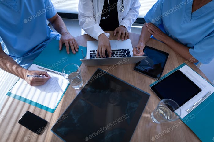 High angle view of multi ethnic surgeons discussing over laptop in clinic at hospital