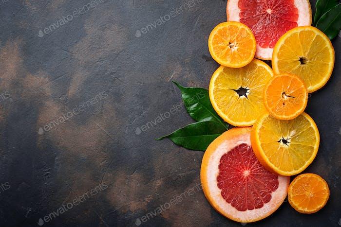 Different sliced citrus on dark concrete background
