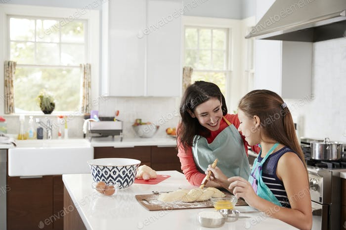 Jewish girl glazing plaited challah bread dough with her mum
