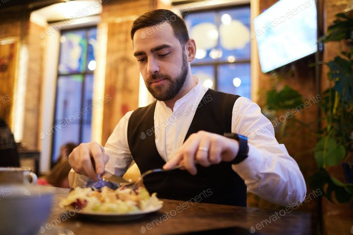 Handsome Businessman Eating in Restaurant