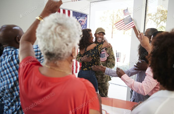 Young black soldier returning home to a surprise family party, selective focus