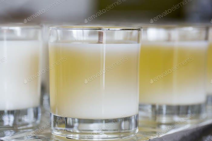 Nahaufnahme von handgefertigten weißen und gelben Glaskerzen mit Holzdocht.