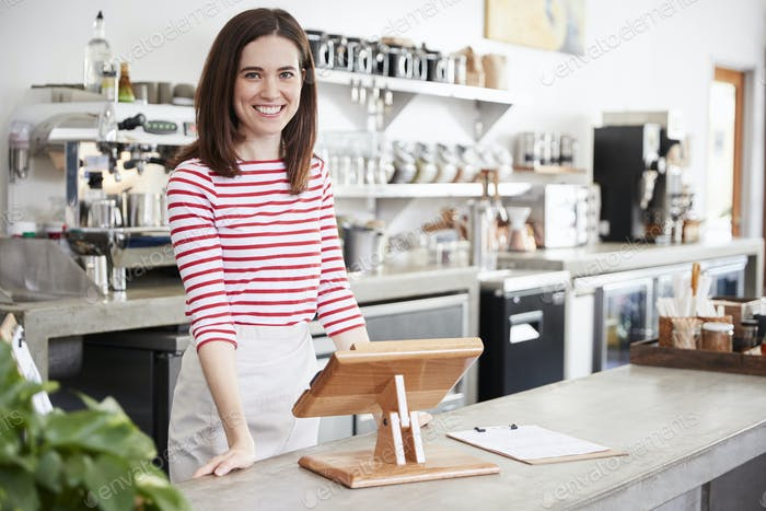 Young female coffee shop owner smiling behind the counter