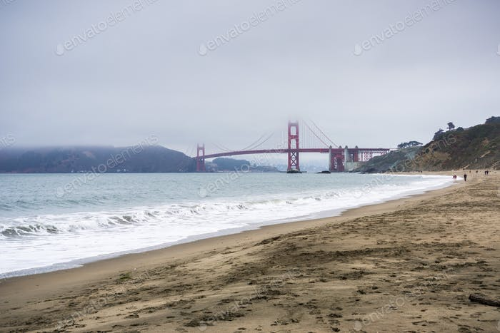 People walking on a sandy beach close to Golden Gate Bridge, San Francisco, California