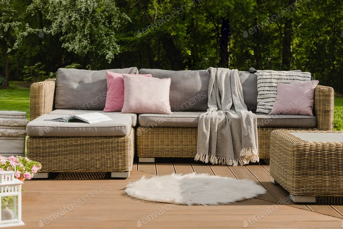 White rug on wooden terrace in stylish garden with wicker furniture with pillows
