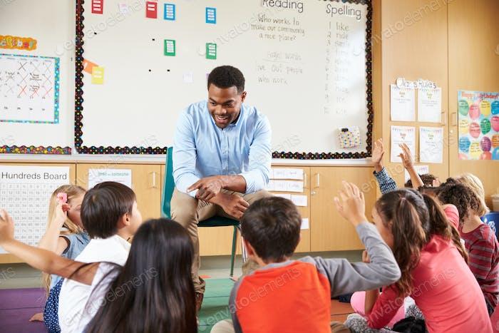 Elementary school kids sitting around teacher in a classroom