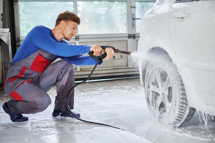 Man worker washing luxury car on a car wash
