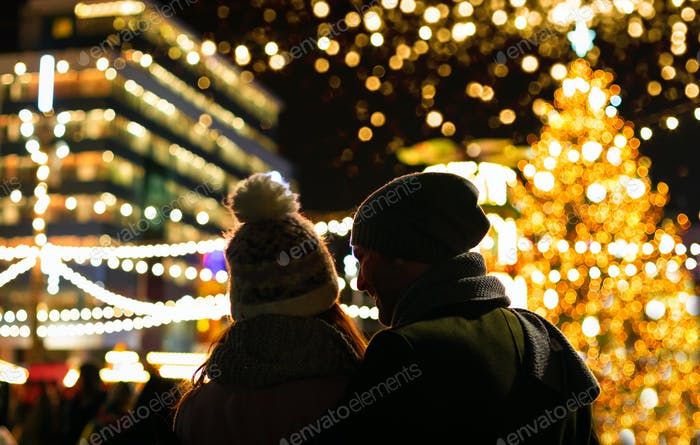 The couple are looking at the decorated Christmas market in the evening