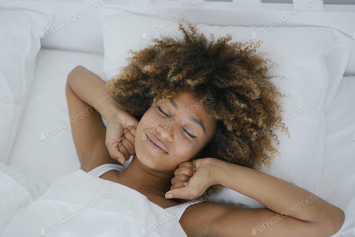 Charming woman awakening happily