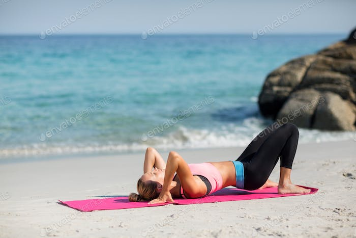 Woman exercising on exercise mat at beach