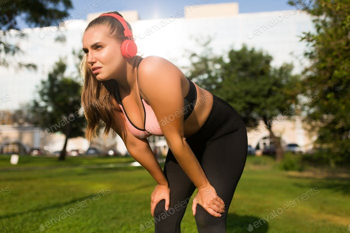 Young plus size woman in sporty top and leggings with red headph