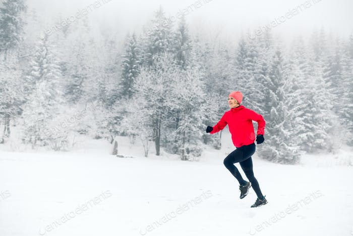 Happy girl running on snow in winter mountains