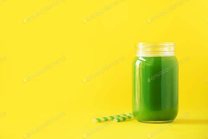 Bottle of green celery smoothie on yellow background. Banner with copy space. Fresh juice for detox