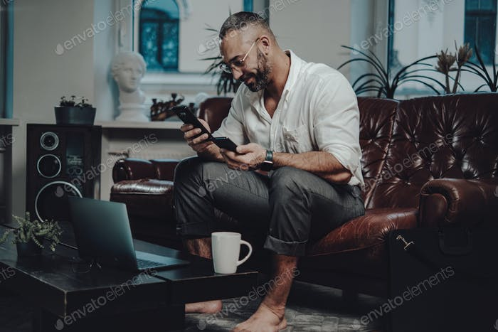 Caucasian entrepreneur with glasses holding two smartphones at sofa