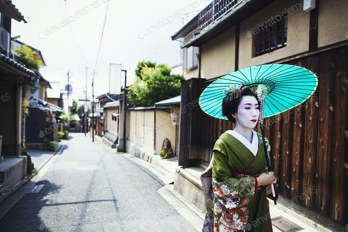 A woman dressed in the traditional geisha style, holding a paper parasol walking along a street.