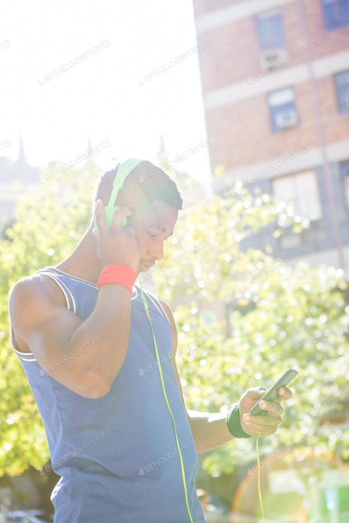 A handsome athlete using his phone on a sunny day