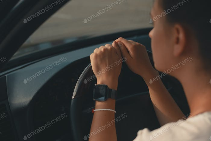 Close-up woman hands on the steering wheel