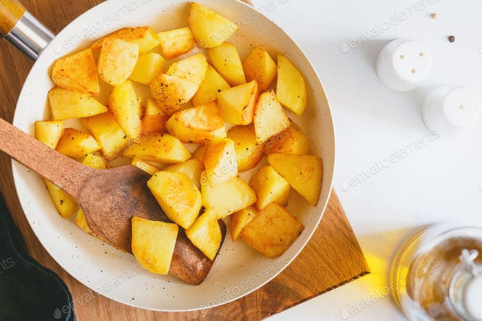 Top view on roasted potato in a white pan on a kitchen table. Modern style, vegetarian food.