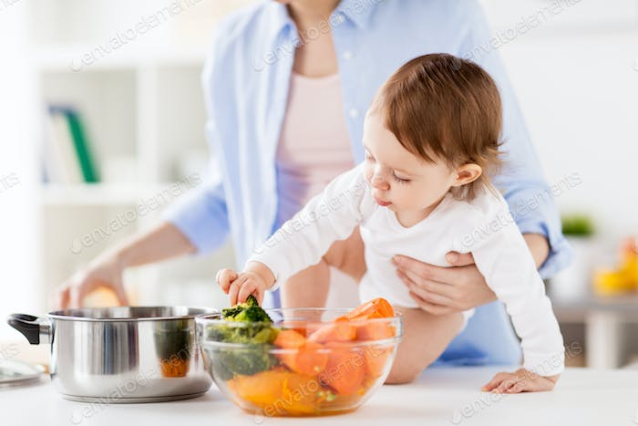 happy mother and baby cooking vegetables at home