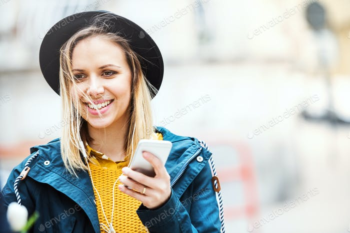 Young woman with smartphone in sunny spring town.