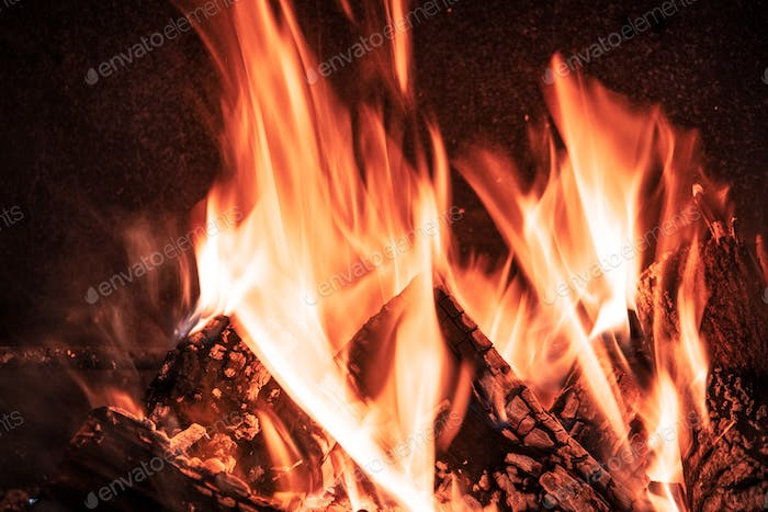 Fire orange tongues on black background in a brick fireplace
