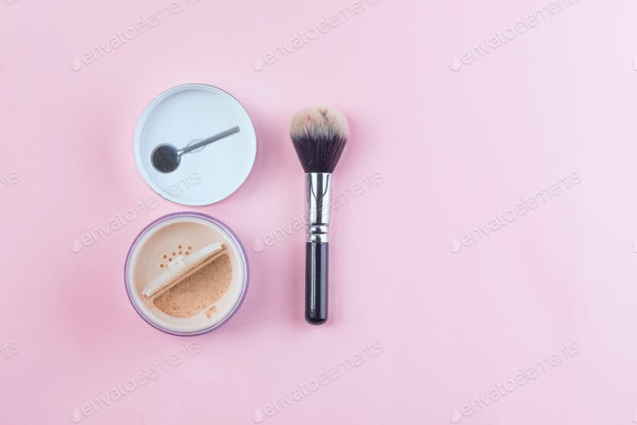 Beige face powder and brush for make up isolated on pink background with copy space, flat lay