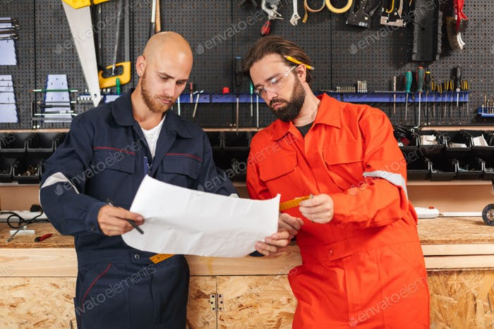 Two builders in work clothes thoughtfully looking on sketch with