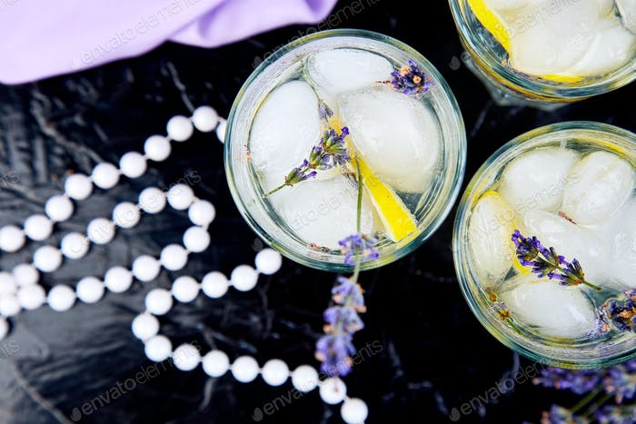 Lavender lemonade with lemon and ice on black background
