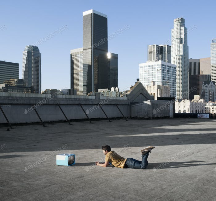 A man lying on his stomach on a city rooftop watching a small blue portable television.