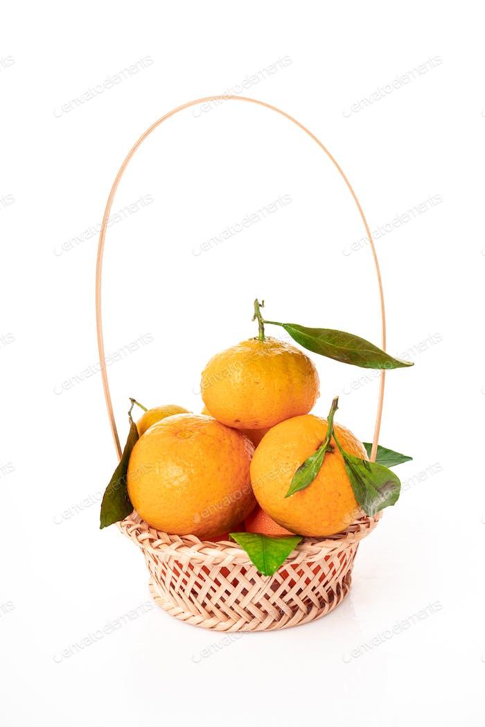tangerines  with leaves in a beautiful basket. organic ripe mandarins