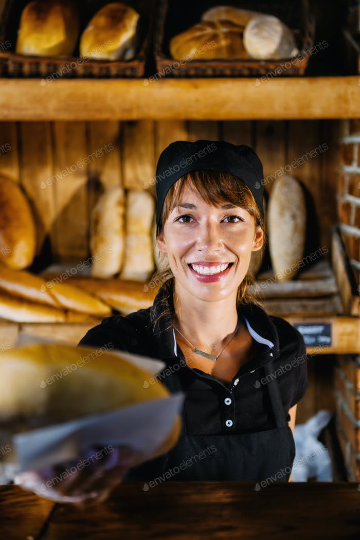 Female Shop Assistant In Bakery Holding Bread