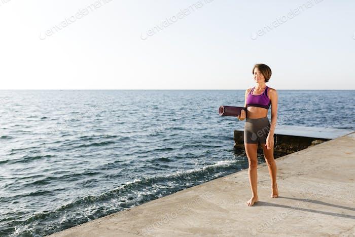 Junge lächelnde Frau mit dunklen kurzen Haaren hält Yoga-Matte in der Hand beim Gehen am Meer