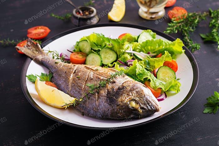 Baked fish dorado with lemon and fresh salad