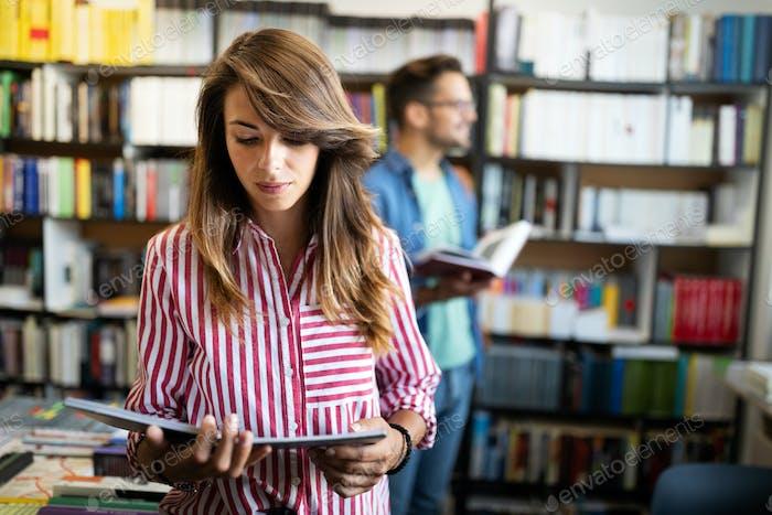 Bildung, Gymnasium, Universität, Lernkonzept. Lächelnd Student Mädchen Buch lesen in der Bibliothek