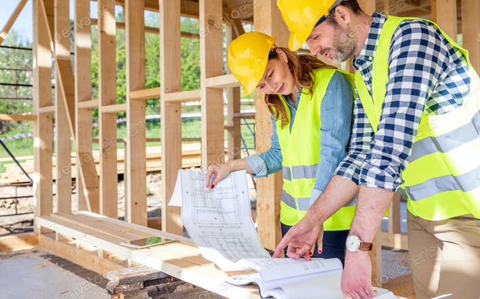 Construction engineer and architect consult plans on building site