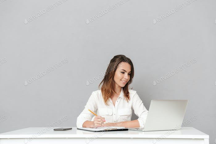 Amazing cheerful young business woman using laptop computer writing notes.