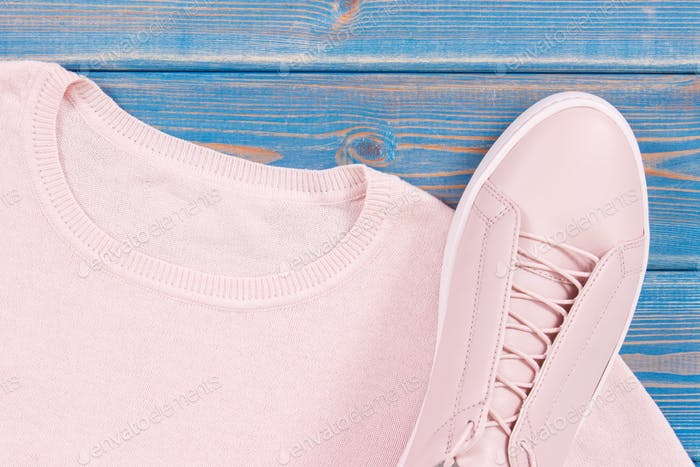 Pink womanly leather shoes and sweater on old blue boards