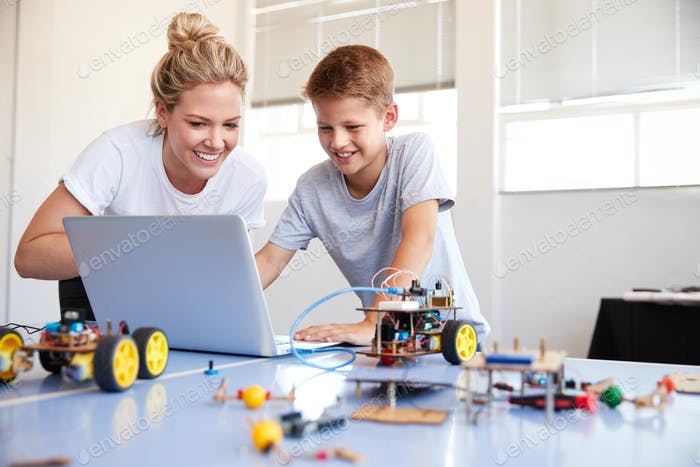 Male Student With Teacher Building Robot Vehicle In After School Computer Coding Class
