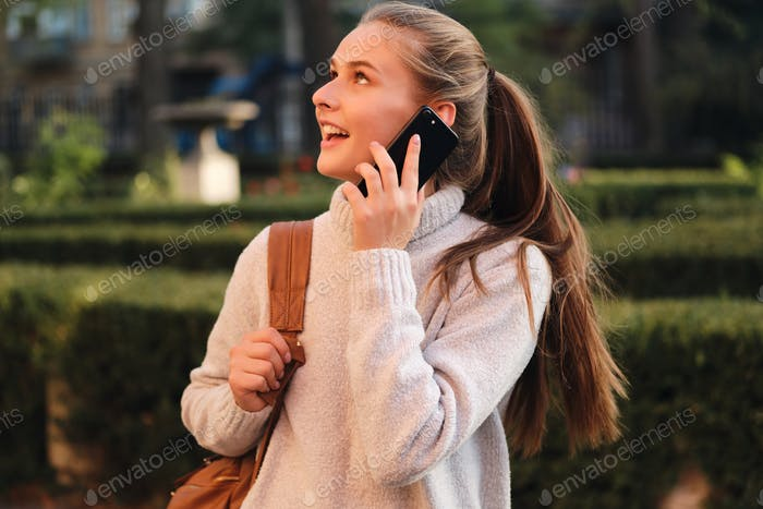 Pretty student girl in cozy sweater with backpack happily talking on cellphone outdoor