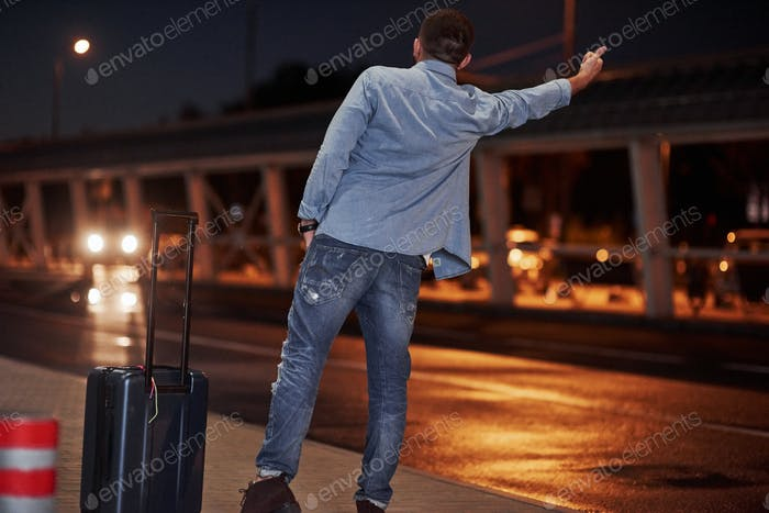 Short-haired man in jeans and a shirt with a baggage tries to catch the car