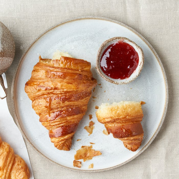 One delicious croissants on plate, hot drink in mug. Morning French breakfast with fresh pastries