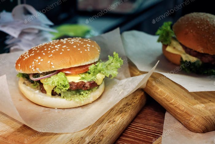 Serving cheeseburger or hamburger with salad and tomatoes onion and cheese on wooden desk